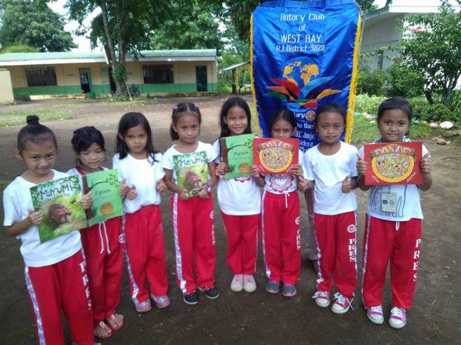 School children with picture books donated by the Rotary Club of West Bay, Laguna